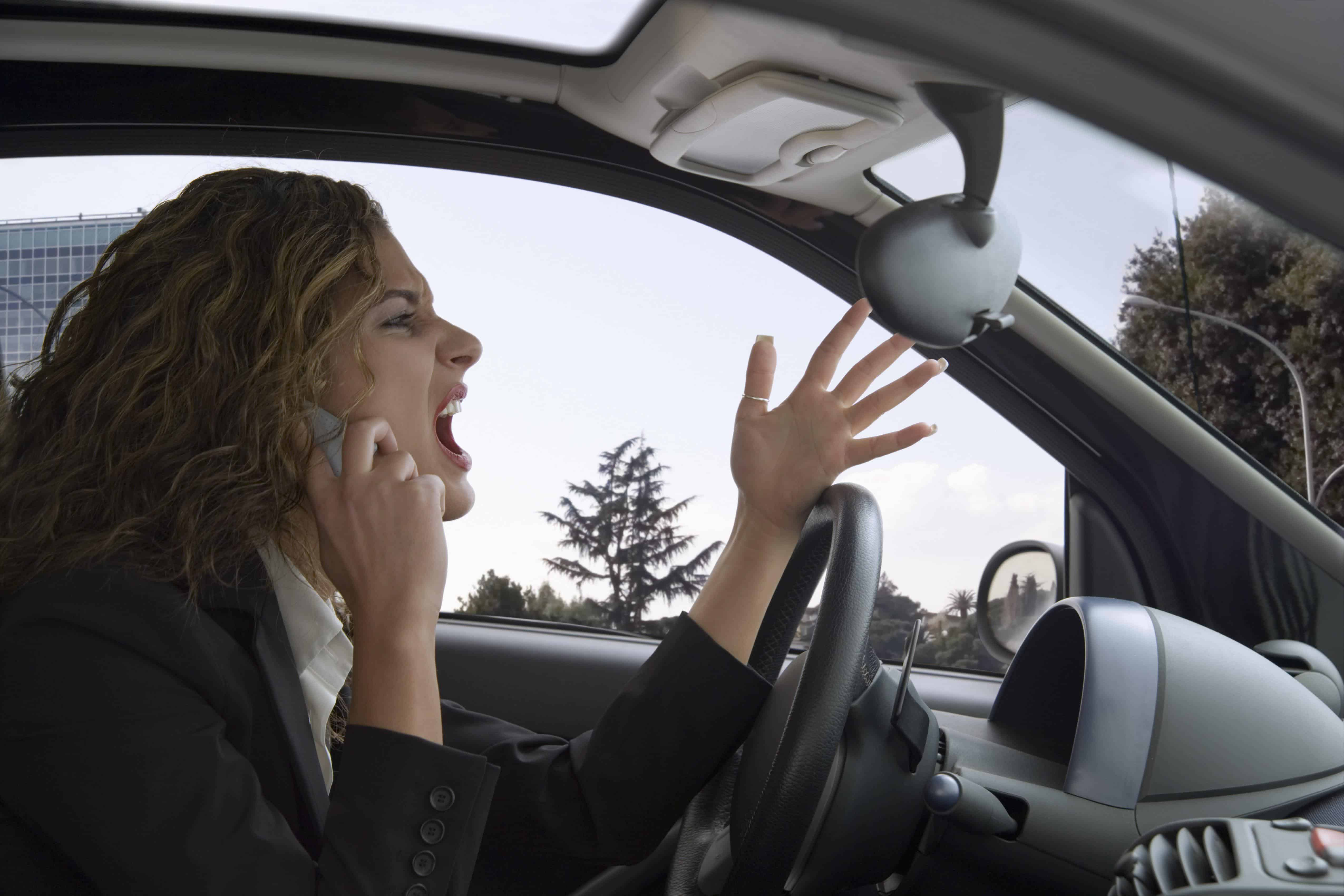 600-02264773 © Siephoto Model Release: Yes Property Release: No Woman Yelling while Driving Car and Using Cell Phone